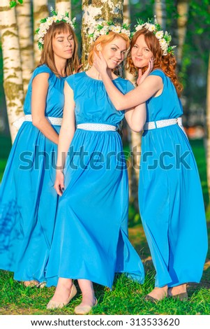 Three beautiful girls on a sunny day in the park - stock photo