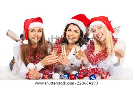 Three beautiful girls on the New Year's Eve champagne - stock photo