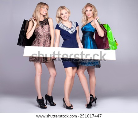 Three beautiful girls shopping. One holding empty board.