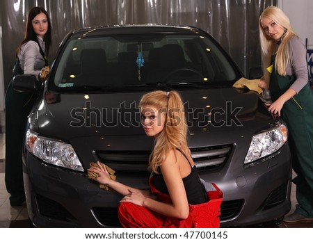 Three beautiful girls wash cars - stock photo