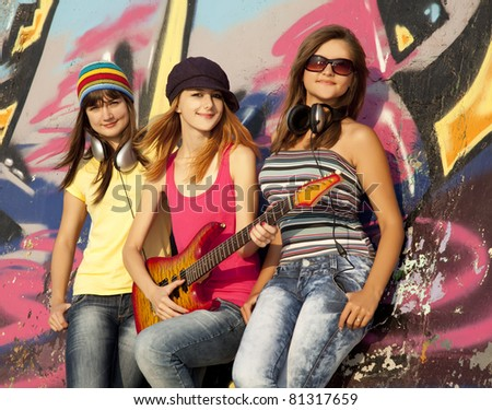 Three beautiful girls with guitar and graffiti wall at background. - stock photo