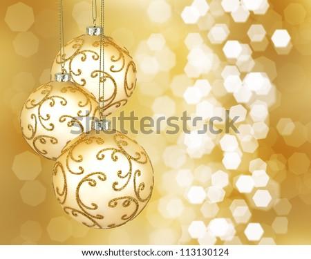 Three beautiful golden christmas balls on a golden background - stock photo