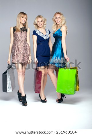 Three beautiful happy blonde woman shopping, posing with bags. Studio shot. - stock photo