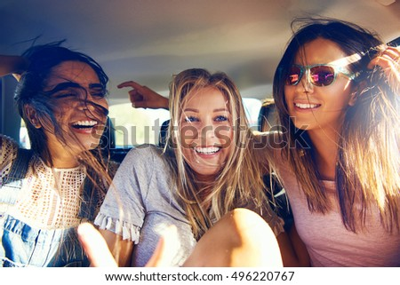 Three beautiful happy girls in a car travelling as passengers on a road trip laughing and joking a they smile at the camera