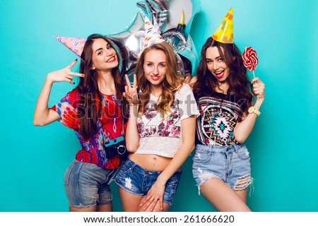 Three beautiful  happy sexy woman  in  stylish summer outfit , paper hats and purity balloons having fun and celebrate  birthday.  Colorful blue background . Pretty girl  hold big lollypop. - stock photo