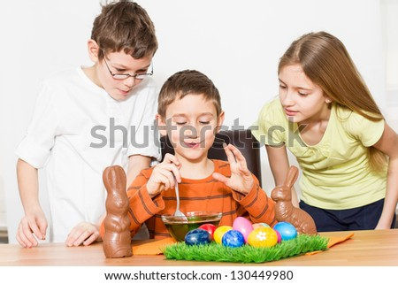 Three beautiful kids painting easter eggs