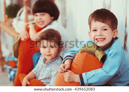 Three beautiful laughing little children in the spring Easter interior photo Studio