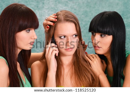 three beautiful nice girls in green dresses  with a mobile phone - stock photo