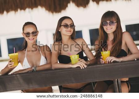 three beautiful sexy women in bikini in bar on Hawaii at beach bar. Beautiful girls enjoying alcoholic beverage cocktail outside. Smiling happy Caucasian women on Hawaiian beach. - stock photo