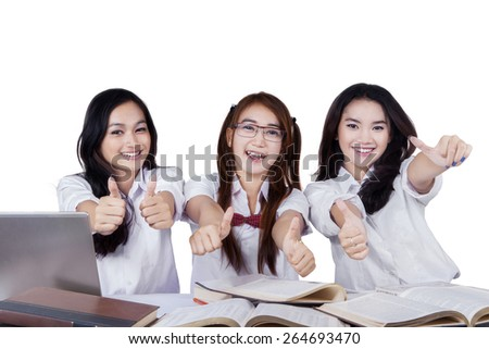 Three beautiful teenage students showing thumbs up at the camera, isolated over white background - stock photo
