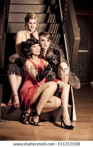 Three Beautiful Vintage Women celebrating at a gathering posed looking at camera - stock photo
