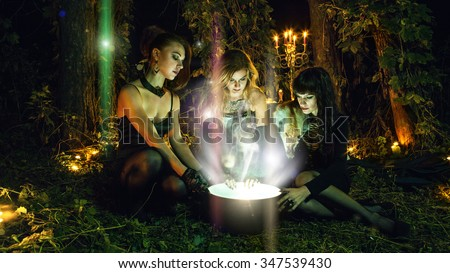 Three beautiful witches are looking in to the magic cauldron. Dark forest on the background. - stock photo