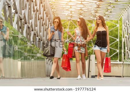 Three beautiful woman on the bridge, hand held shopping bags - stock photo