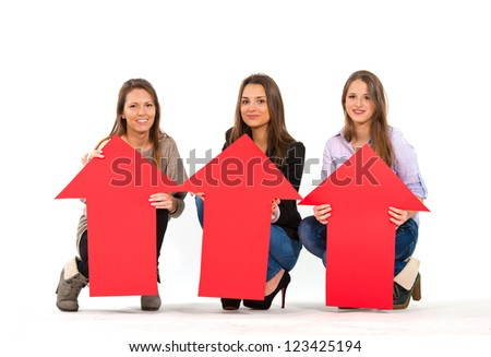 Three beautiful women holding arrows pointing up - stock photo