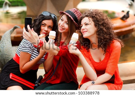 three beautiful women photographing themselves eating icecream - stock photo