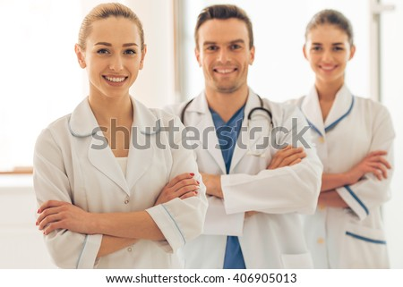 Three beautiful young doctors are looking at camera and smiling, standing in line with crossed arms in hall of the hospital