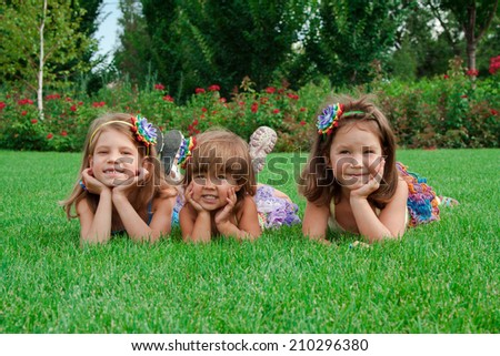 Three beautiful young girl lying on the lawn in the summer
