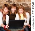 Three beautiful young students waiting for coffee and checking news on laptop - stock photo