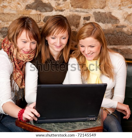 Three beautiful young students waiting for coffee and checking news on laptop