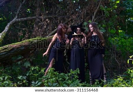 three beautiful young witches in black dresses - stock photo