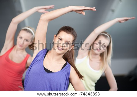 Three beautiful young woman doing aerobics exercises - stock photo