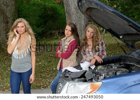 Three beautiful young woman stand in front of car with hood up - roadside assistance for broken down car - one calling for help on cell phone - stock photo