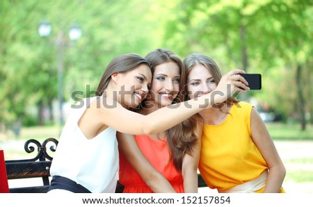 Three beautiful young woman  taking picture in summer park - stock photo