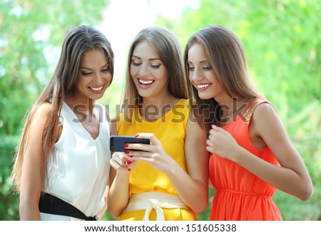 Three beautiful young woman  with smartphone in summer park  - stock photo