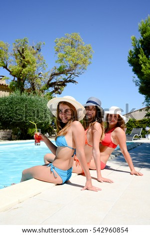 three beautiful young woman with sun hat sitting by the poolside of a resort swimming pool during summer holiday