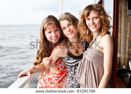 Three beautiful young women a Caucasians standing together on the deck of yacht in cruise - stock photo
