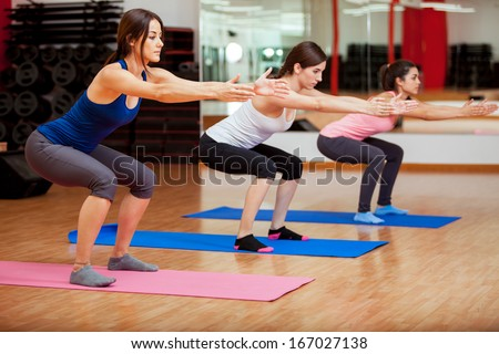 Three beautiful young women doing some squats and exercising at a gym - stock photo