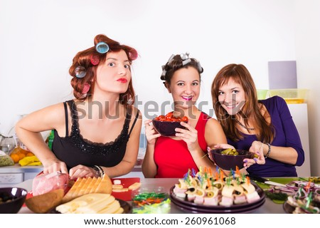 Three beautiful young women housewifes cooking together - stock photo