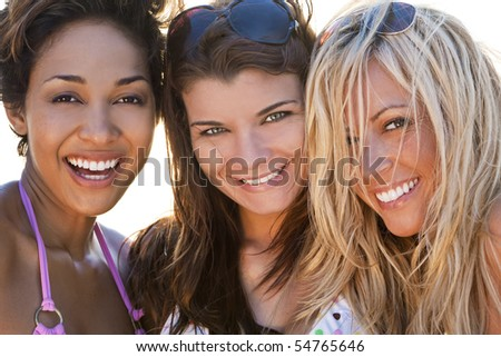 Three beautiful young women in their twenties laughing and having fun at a beach, selfie photograph shot in golden evening sunshine. - stock photo