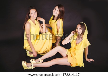 Three beautiful young women in yellow dresses posing on black background. Studio portrait of trio of pretty girls wearing trendy dresses and yellow shoes. Isolated on black background.