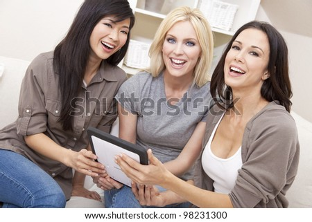 Three beautiful young women or girl friends at home using tablet computer and laughing - stock photo