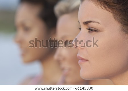 Three beautiful young women photographed in profile, the focus is on the woman in the foreground
