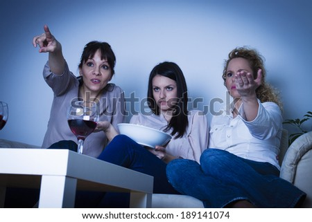 Three beautiful young women sitting on the sofa, watching tv - stock photo