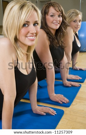 Three beautiful young women stretching at the gym