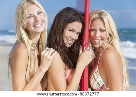 Three beautiful young women surfer girls in bikinis laughing having fun with red surfboard at a beach