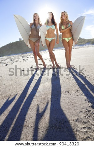 Three beautiful young women surfer girls in bikinis with white surfboards at a beach - stock photo