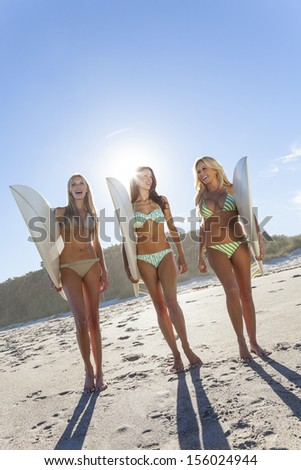 Three Beautiful young women surfer girls in bikinis with white surfbords at a beach - stock photo