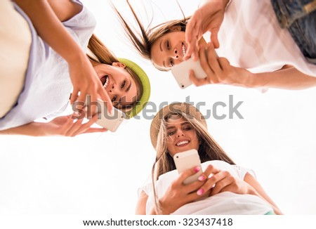 Three beautiful young women walk in the city, using phone outdoors - stock photo