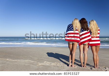 Three beautiful young women wearing bikinis and wrapped in American flags on a sunny beach - stock photo