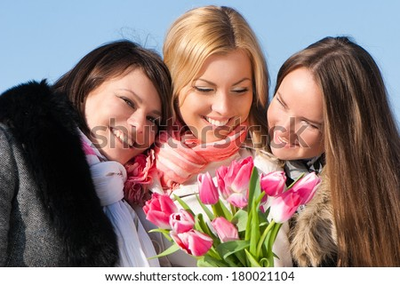 Three beautiful young women with pink tulips  - stock photo
