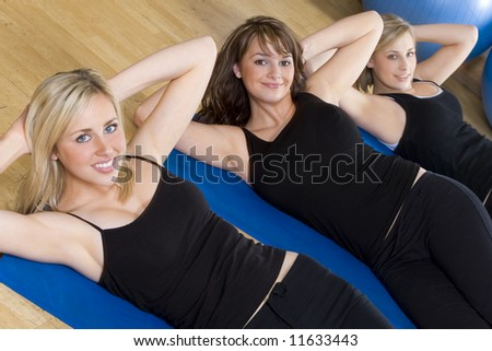 Three beautiful young women working out at the gym, the focus is on the brunette girl in the center