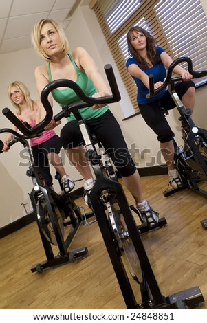 Three beautiful young women working out on  bikes at the gym