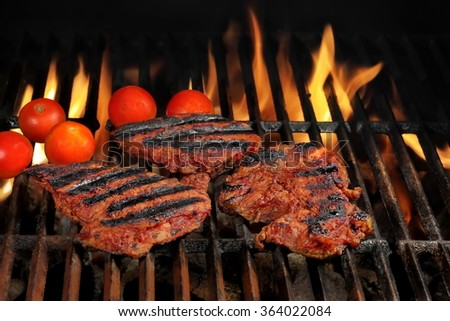 Three Beef Steaks And Tomato On The Hot Flaming BBQ Charcoal Grill With Bright Flames Isolated On Black Background. Cookout Or Summer Party Or Picnic Concept. Top View - stock photo