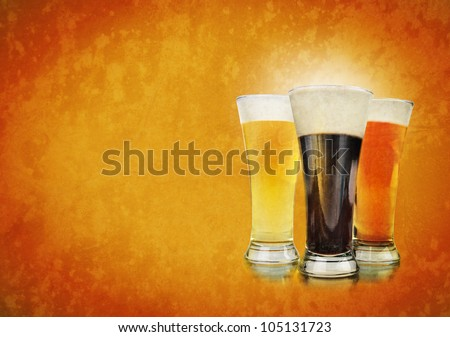 Three beer glasses have foam and are on a golden background with a rough texture. Use it for a Bar or celebration concept.