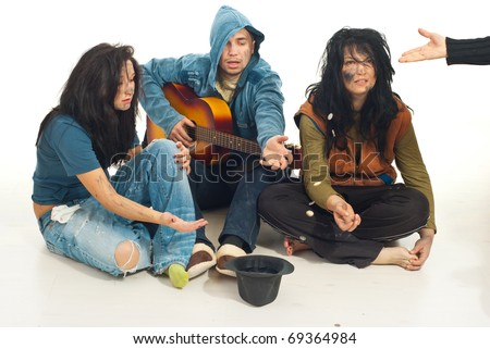 Three beggars singing with guitar and receive coins from someone in their hat - stock photo