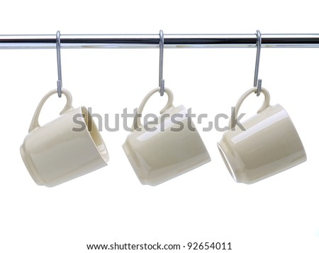 Three beige coffee cups hanging on metal railing on white background - stock photo